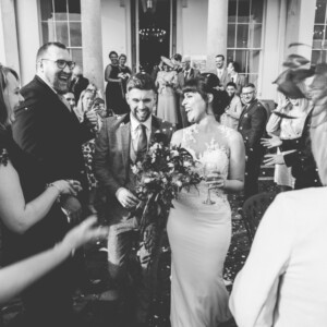 Black and white photo of bride and groom, confetti being thrown at Exeter wedding venue