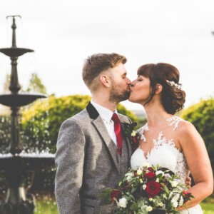 Bride and Groom kissing by water fountain at Exeter wedding venue in Devon